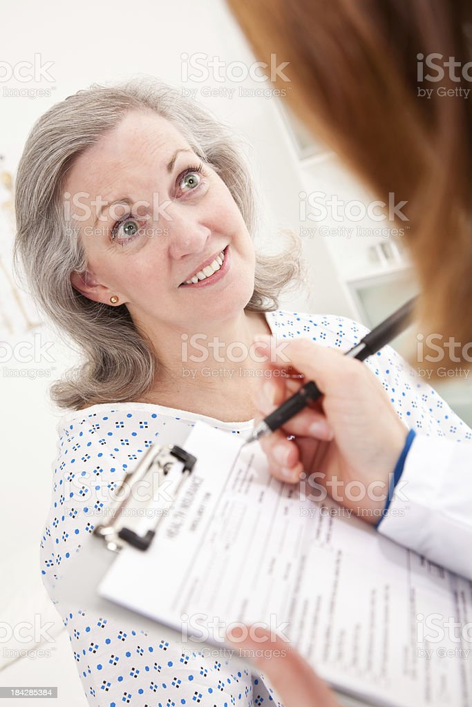 Surprised Mature Female Patient With Doctor Filling Out Form royalty-free stock photo