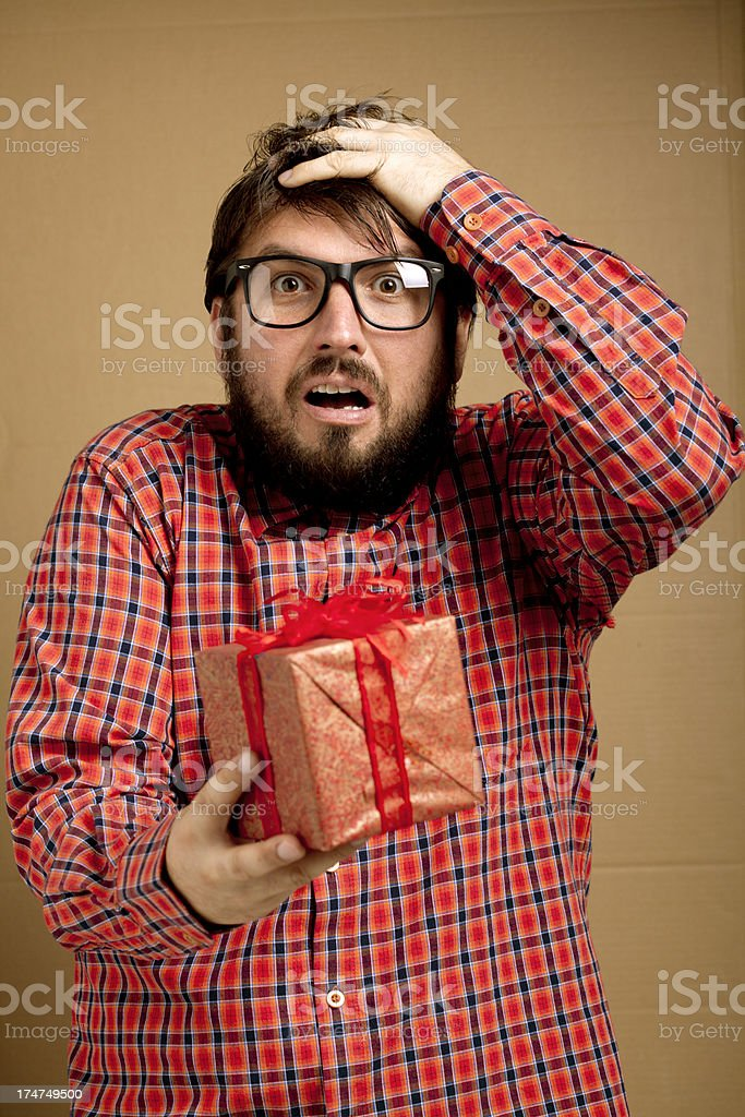 Surprised nerd gay holding present royalty-free stock photo