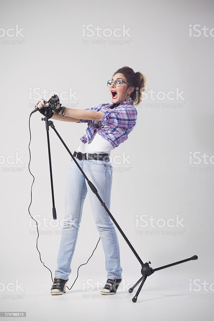 Surprised nerdy female singer with glasses holding microphone royalty-free stock photo