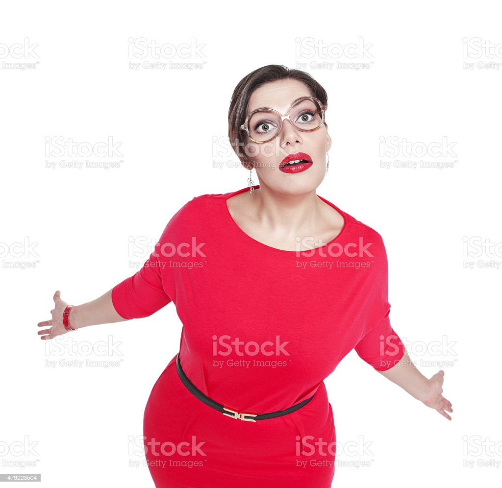 Surprised plus size woman in glasses shrugs her shoulders stock photo