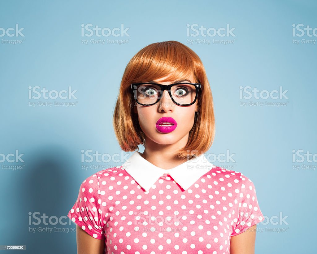 Surprised red hair young woman wearing polka dot dress stock photo