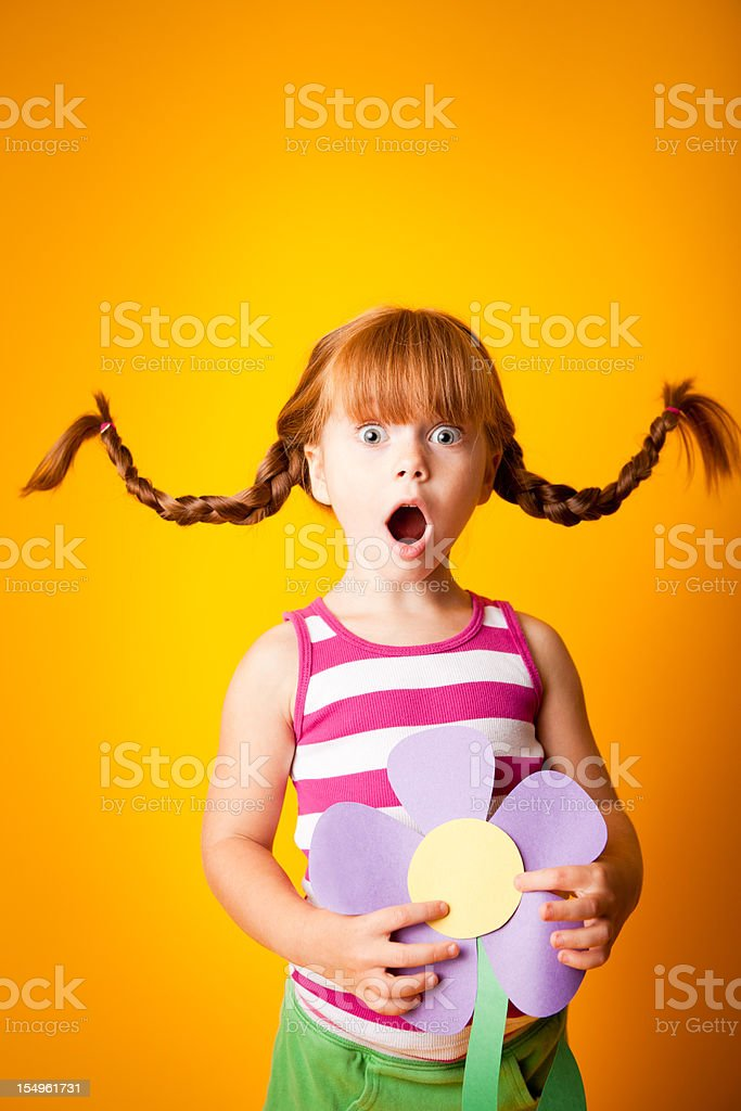 Surprised, Red-Haired Girl with Upward Braids and Oversized Flower stock photo