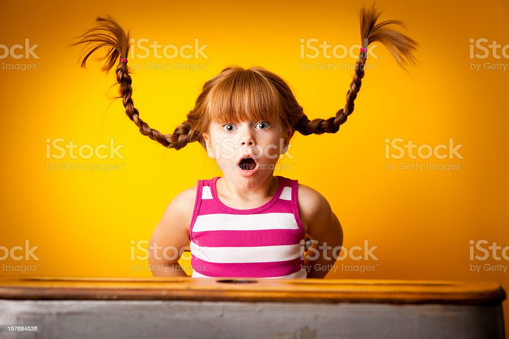 Surprised Red-Haired Girl with Upward Braids in School Desk stock photo