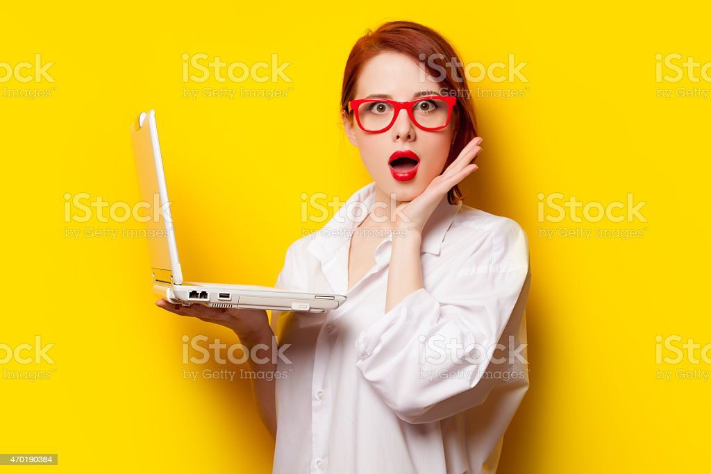 Surprised redhead girl in oversized white shirt holding a PC stock photo