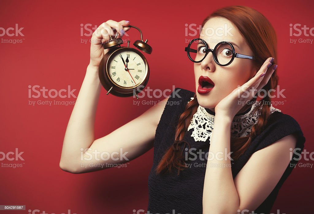 Surprised redhead girl with clock. stock photo