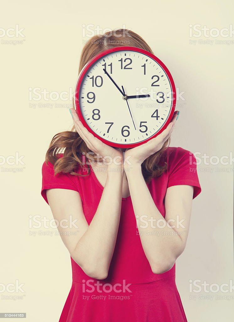 Surprised redhead girl with huge alarm clock on light background stock photo