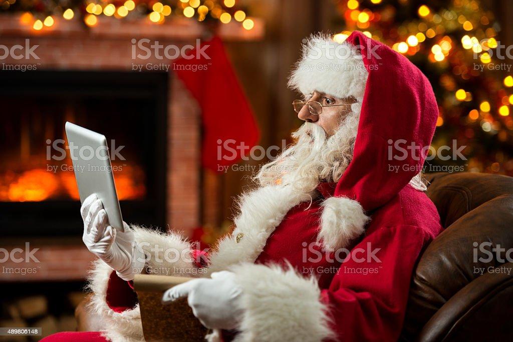Surprised Santa Claus using digital tablet at home. stock photo