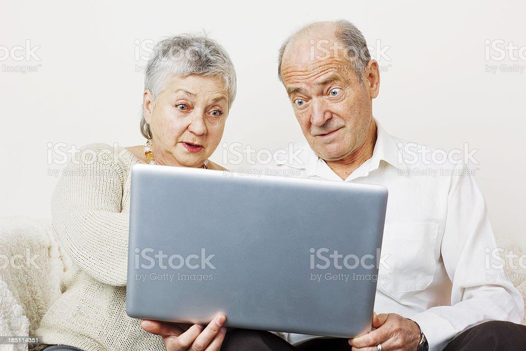 Surprised Senior Couple Learning to use Laptop royalty-free stock photo