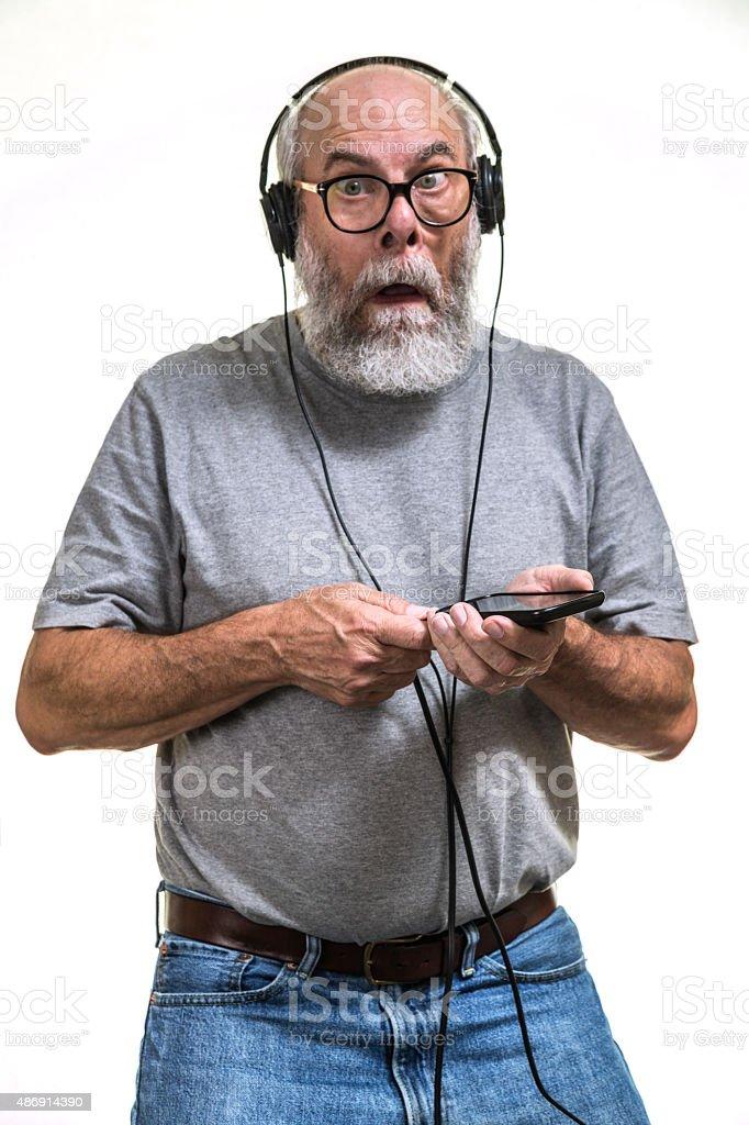 Surprised Senior Man Plugging Music Headphones Into Smartphone stock photo