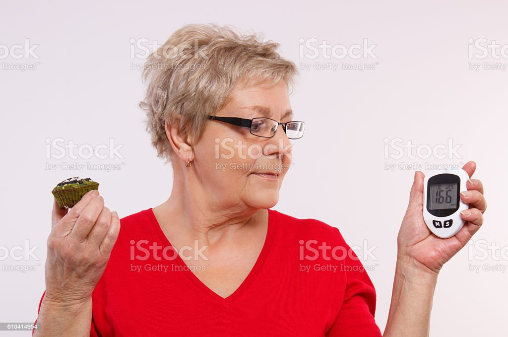 Surprised senior woman holding glucometer and fresh cupcake stock photo