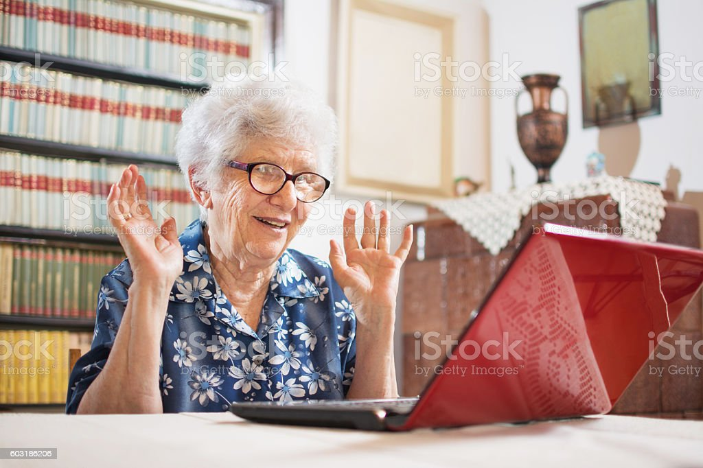 Surprised senior woman sitting in front of laptop at home. stock photo