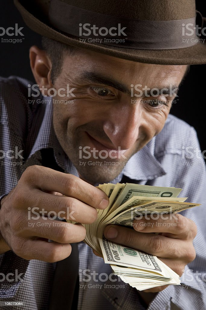 Surprised Smiling Man Wearing Hat Counting Dollar Bills royalty-free stock photo