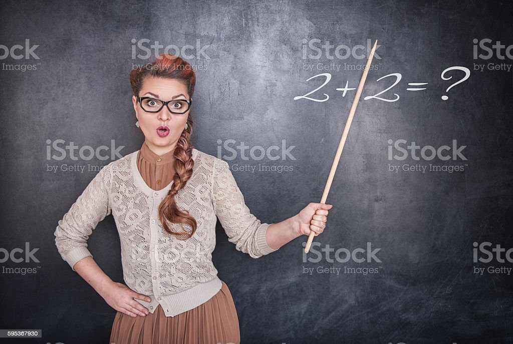 Surprised teacher with pointer on chalkboard background stock photo