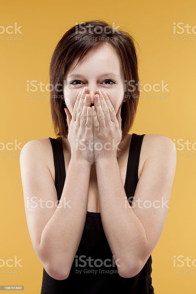 surprised teenage girl covering mouth with her hands royalty-free stock photo