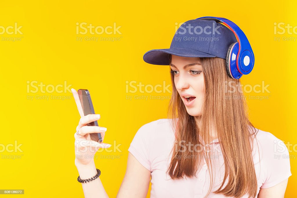 Surprised teenage girl uses a headphones and mobile phone stock photo