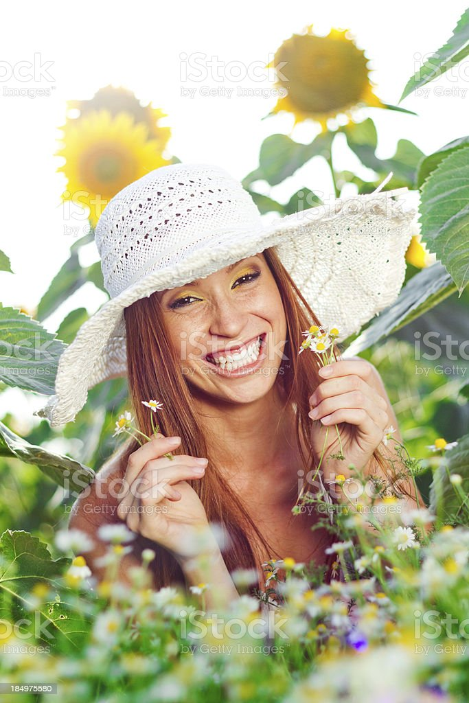 Surprised toothy smile of funny young woman holding daisies royalty-free stock photo