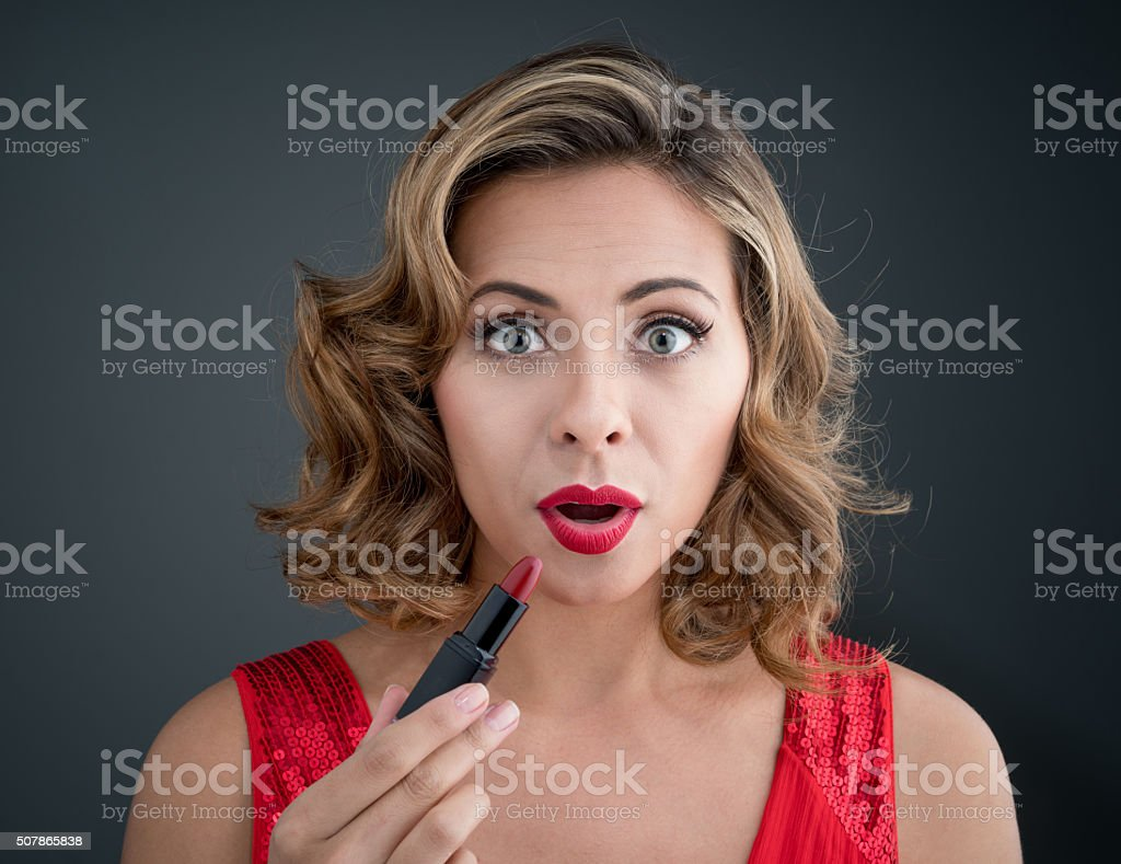 Surprised woman applying red lipstick stock photo