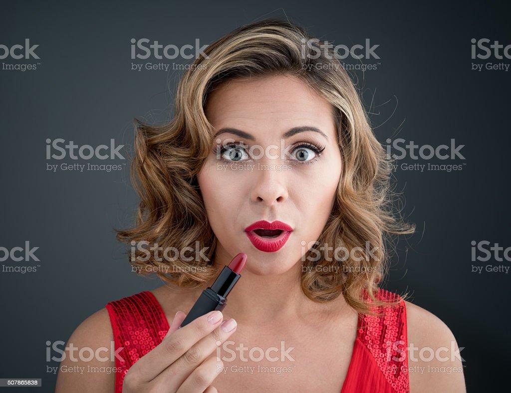 Surprised woman applying red lipstick stock photo