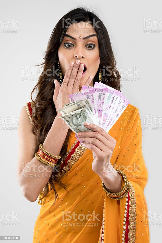Surprised woman holding Indian paper currency stock photo