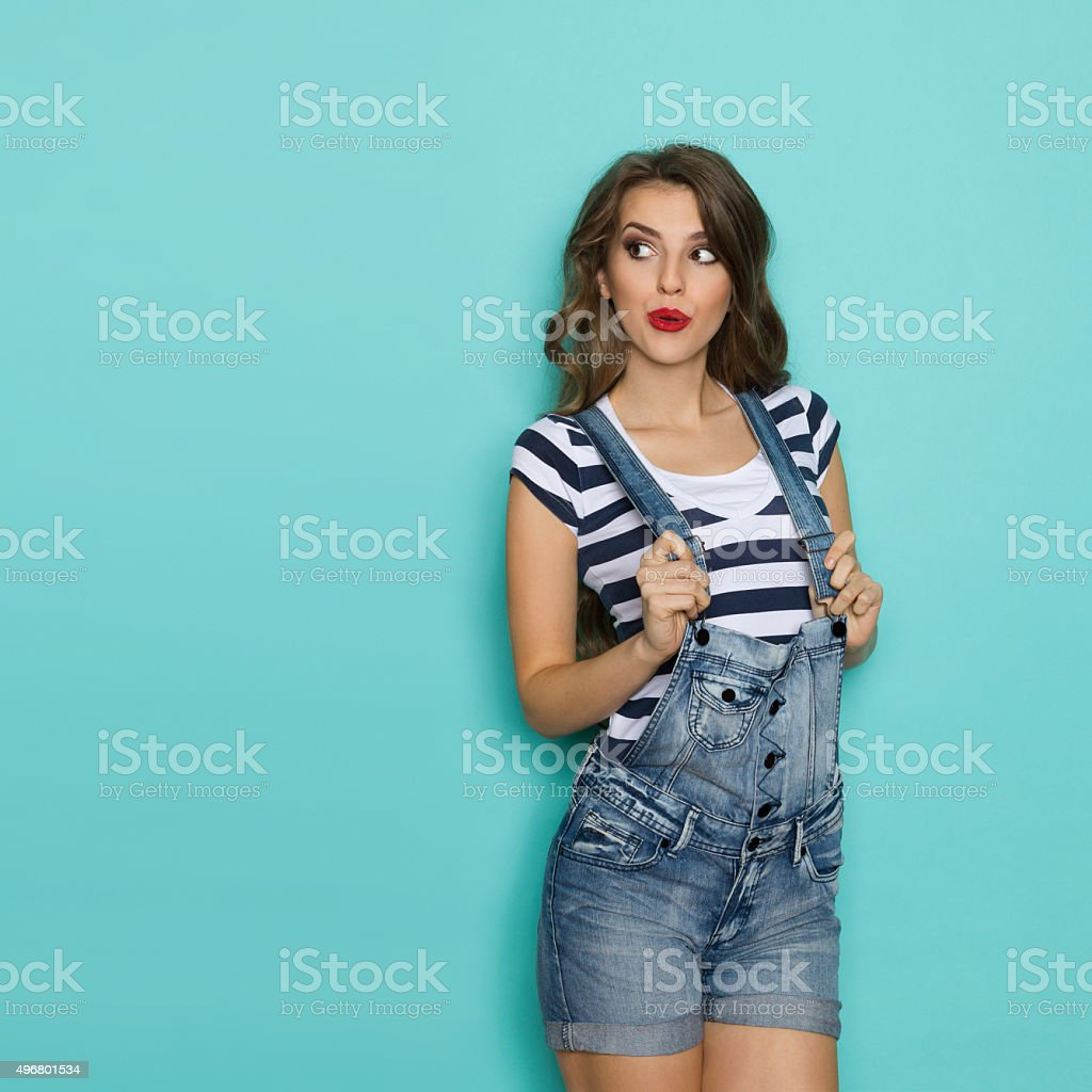 Surprised Woman In Dungarees Looking At Copy Space stock photo