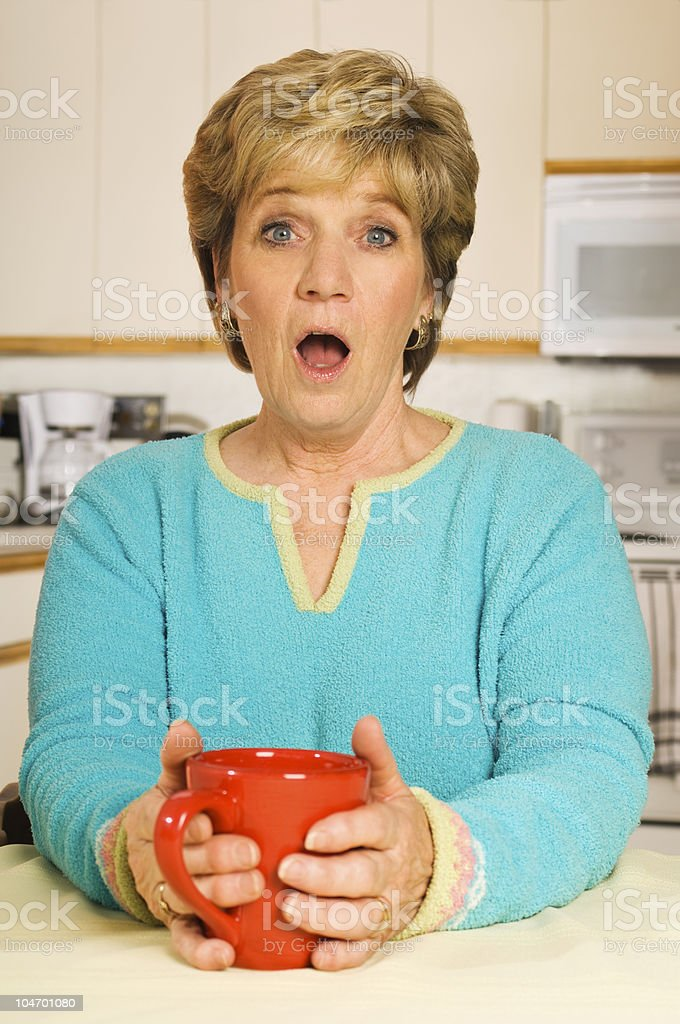 Surprised woman in kitchen holding coffee mug royalty-free stock photo