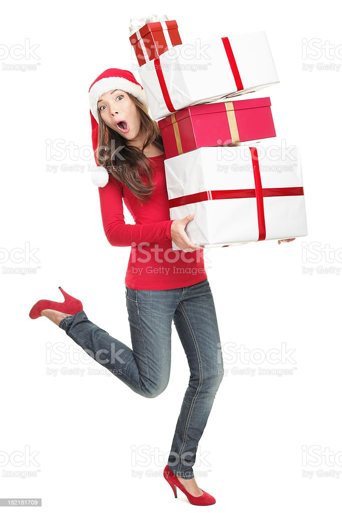 Surprised woman in Santa hat running with gifts stock photo