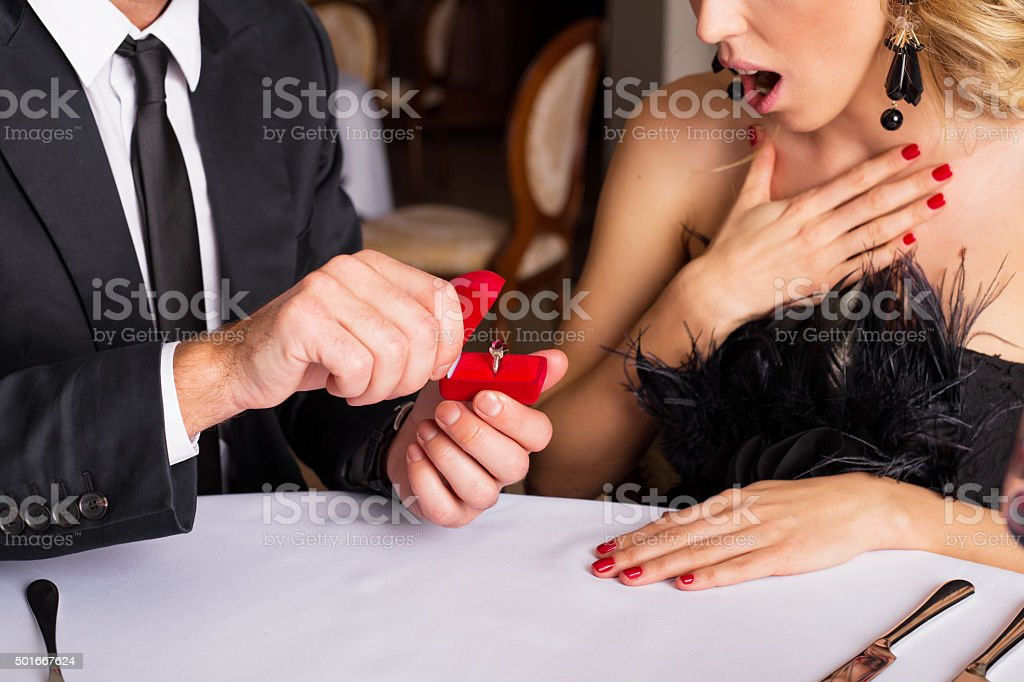 Surprised woman looking at engagement ring stock photo