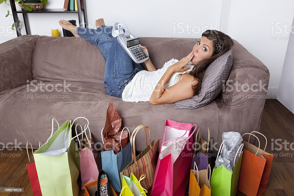 Surprised woman lying on couch with adding machine and shopping royalty-free stock photo