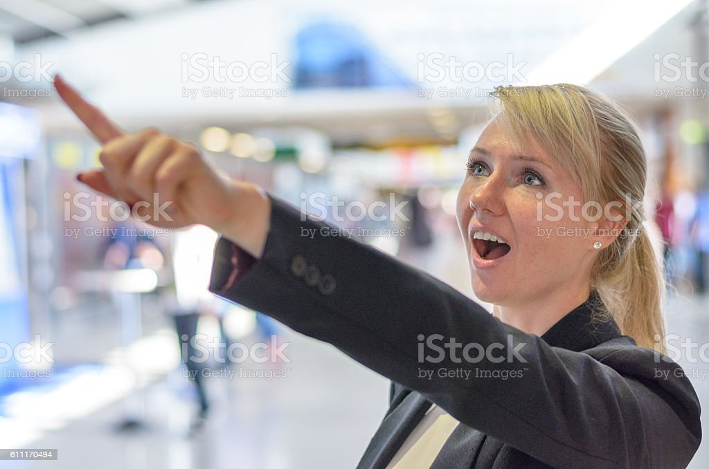 Surprised woman pointing upwards stock photo