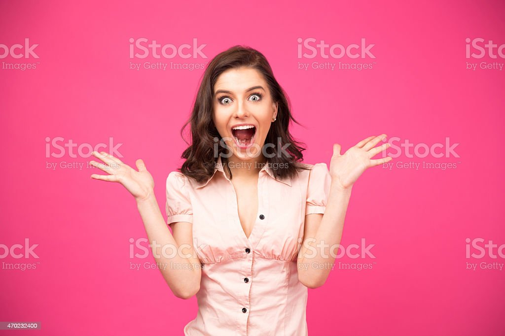 Surprised woman shouting over pink background stock photo