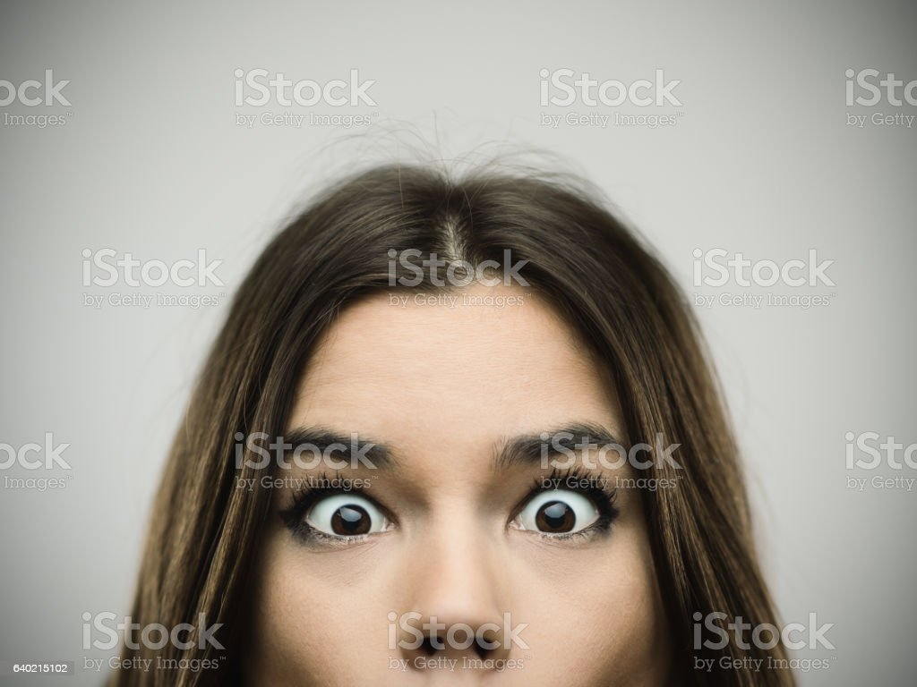 Surprised woman smiling against gray background stock photo