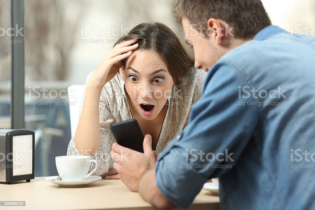 Surprised woman watching media in a smart phone stock photo