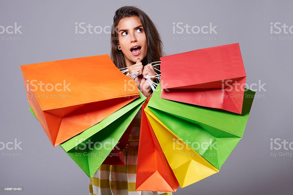 Surprised woman with abundance of shopping bags stock photo