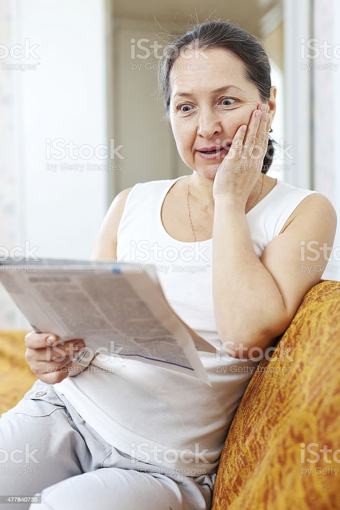 surprised woman with newspaper royalty-free stock photo