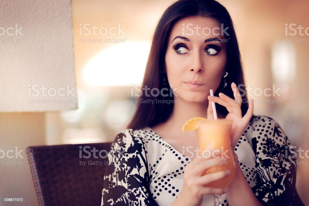 Surprised Woman With Orange Juice in a Restaurant stock photo