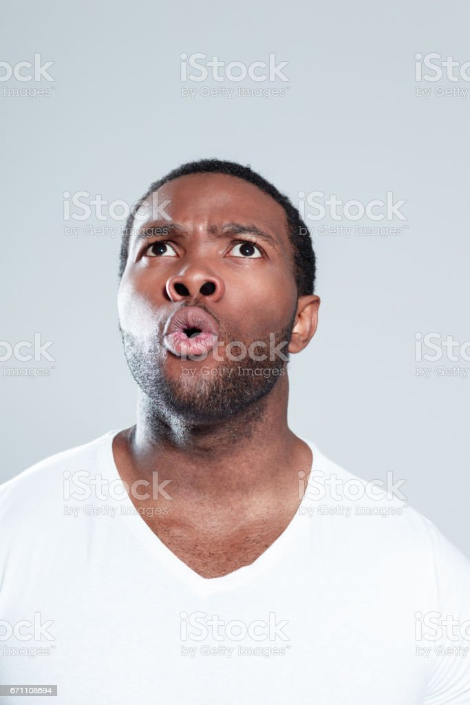 Surprised young african man looking away stock photo