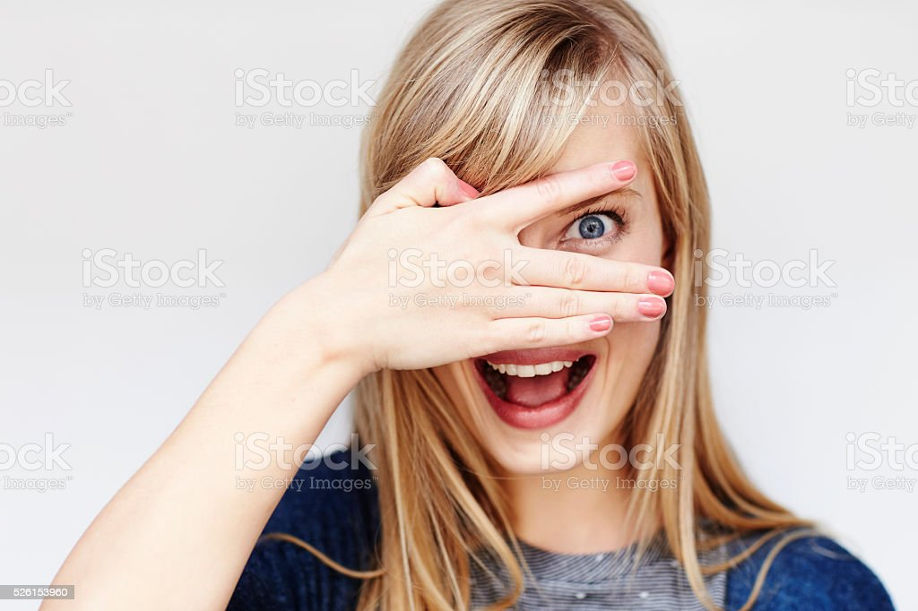 Surprised young blond woman peering though fingers stock photo