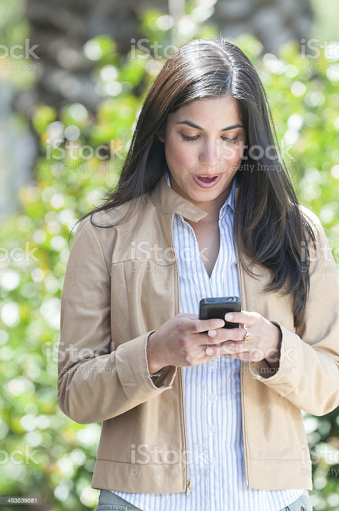 Surprised Young Hispanic Woman Looking at Cell Phone royalty-free stock photo
