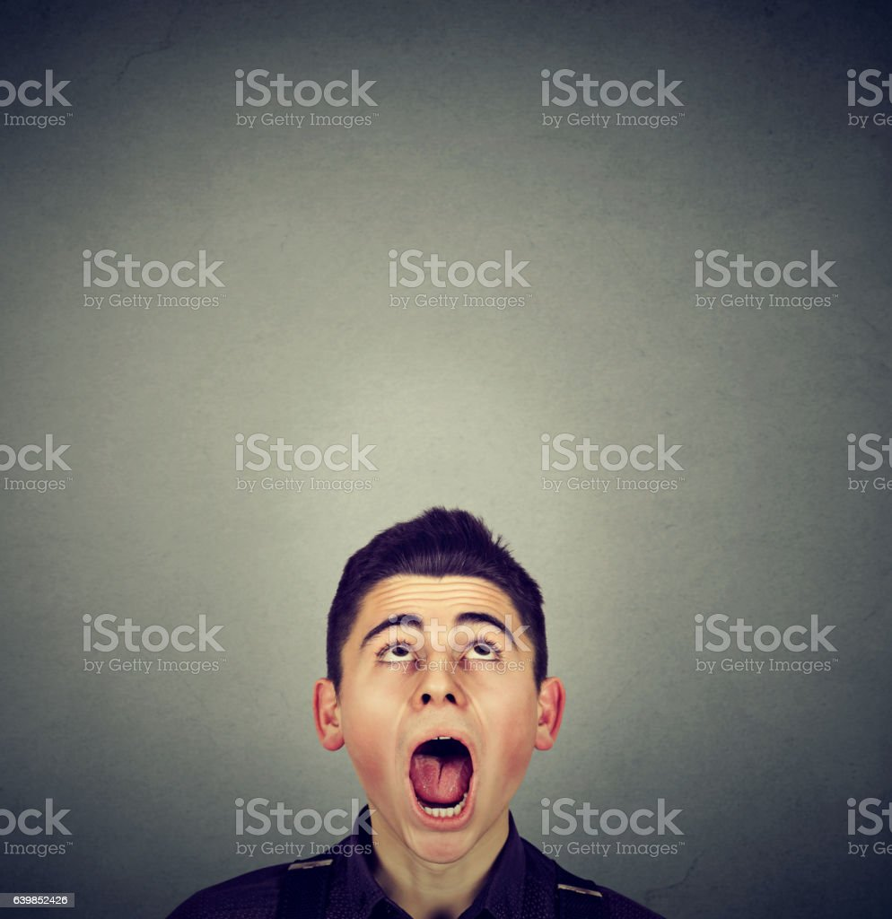 Surprised young man looking up stock photo