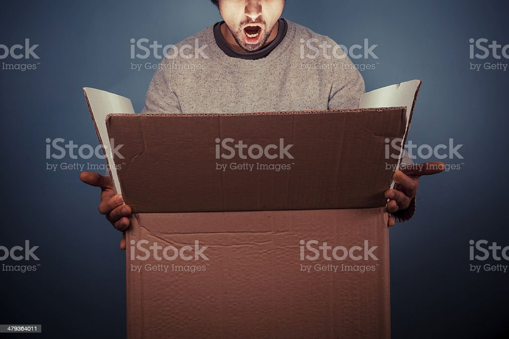 Surprised young man opening exciting box stock photo