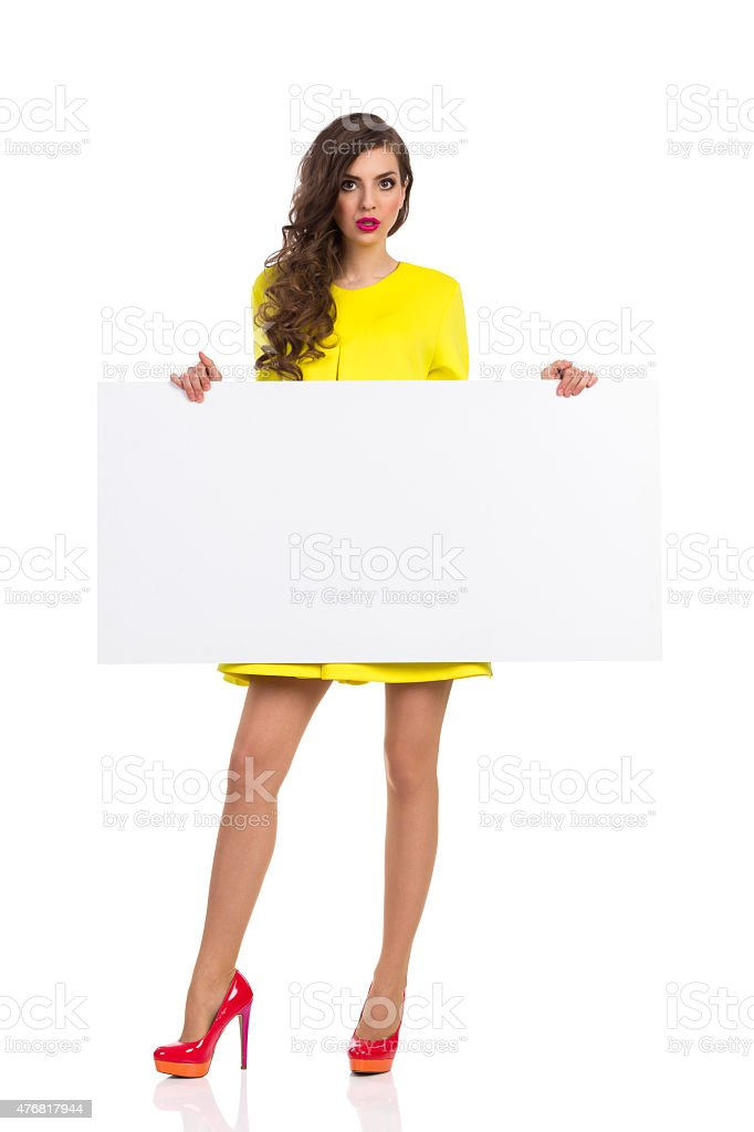 Surprised Young Woman Holding White Poster stock photo