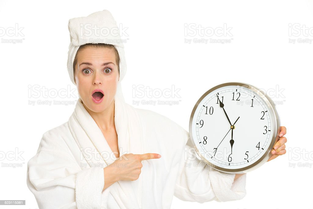 surprised young woman in bathrobe pointing on clock stock photo