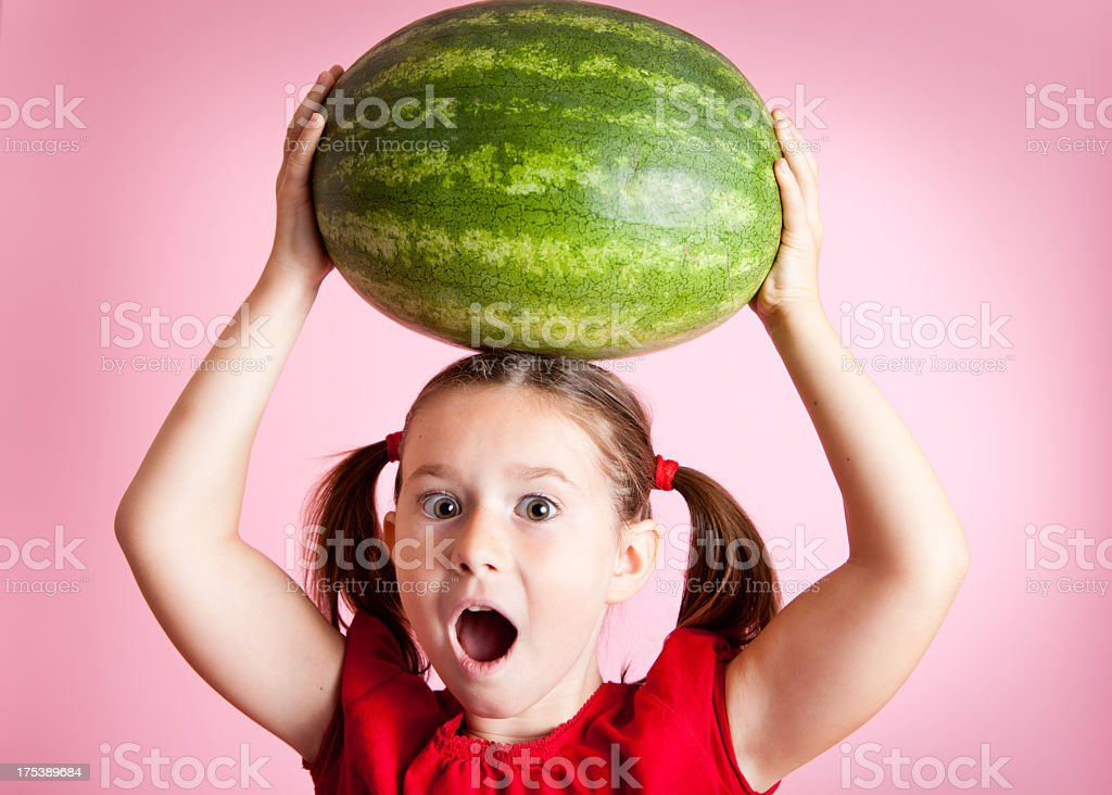 Surprised/Excited Young Girl Holding Watermelon Above Her Head royalty-free stock photo