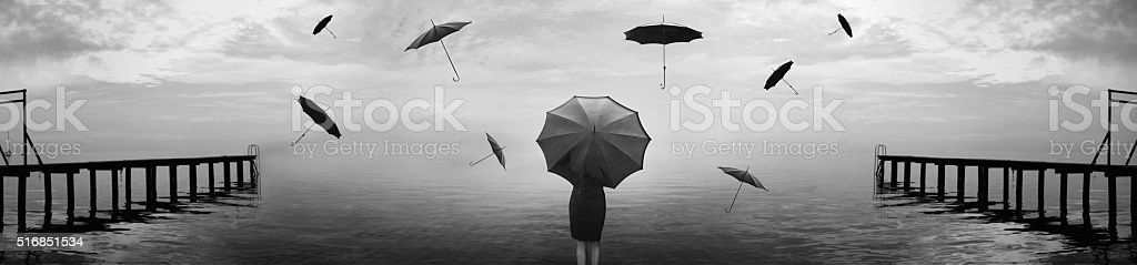 surreal rain of umbrellas on the sea stock photo