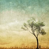 Surreal single tree on cloudy sky with copy space.