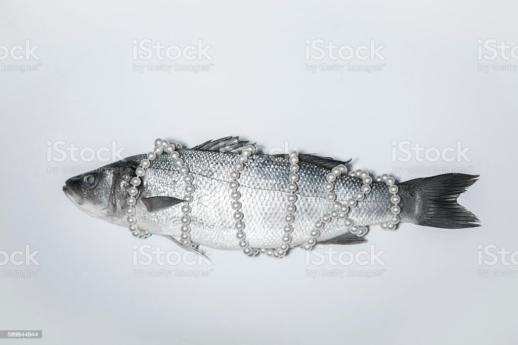 Surrealistic isolated fish with a pearl necklace, Magritte inspired stock photo