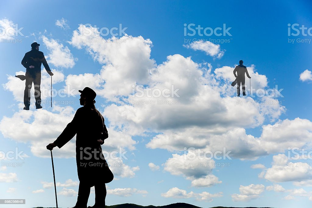 Surrealistic men silhouettes climbing up the clouds in the sky stock photo