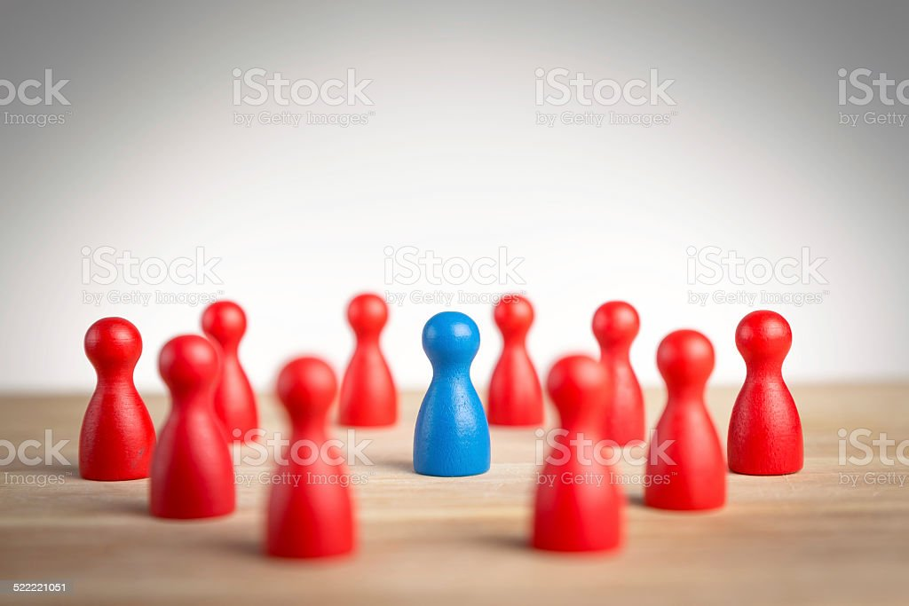 Surrounded by adversity or praised for being different concept stock photo
