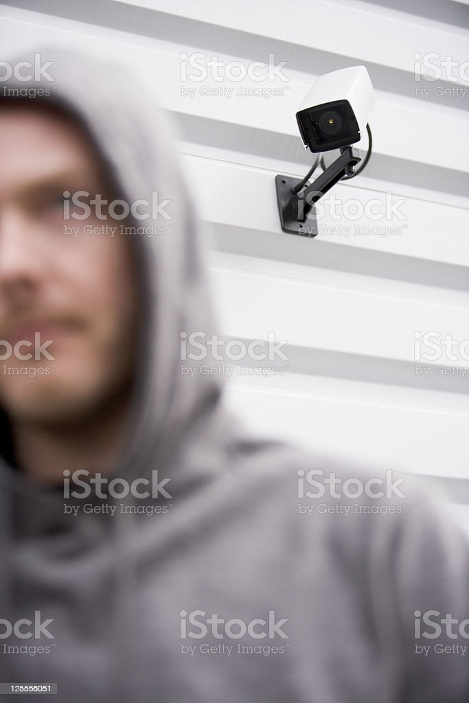 Surveillance Camera And Young Man In Hooded Sweatshirt royalty-free stock photo