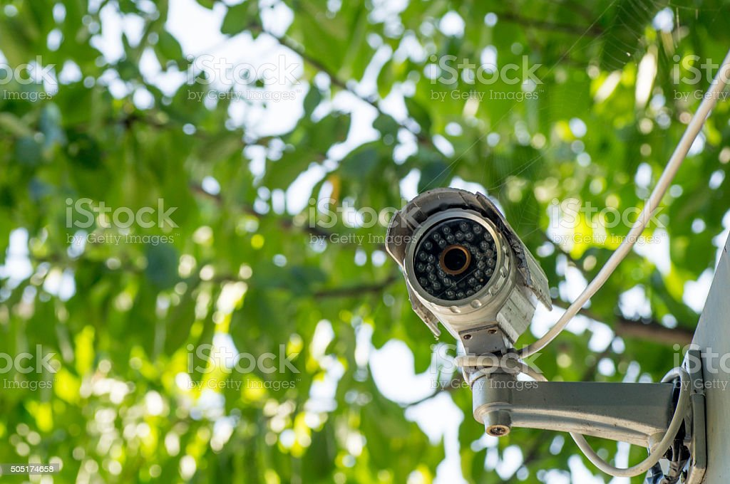Surveillance camera attached to the edge of the roof stock photo